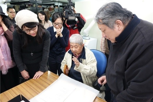 Mr. Tian-yi Chao (center) examines the manuscript she donated to the Special Collection Division of the NCL
