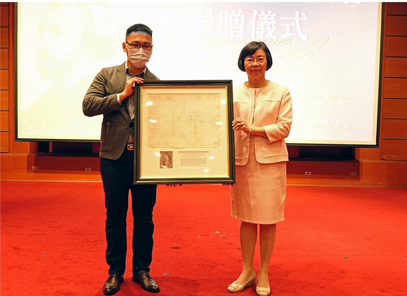Chengdingtang representative Jason Dou (left), treating a letter from first US president, George Washington, as emblematic of the donation ceremony, presents it to Director-General Tseng of the National Central Library
