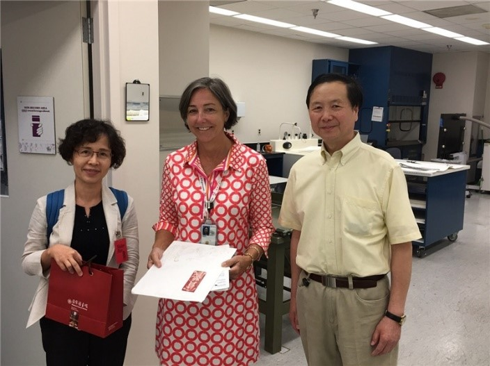 Director of the NCL Bibliographic Information Center, Ching-fen Hsu (left), visits the U.S. National Archives, and on behalf of the NCL presents conservator Terry Boone (center) with a publication