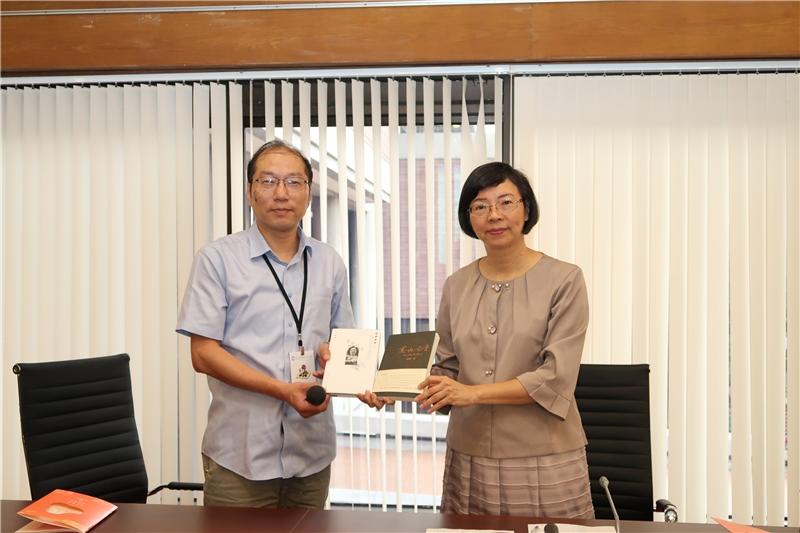 The representative gives the NCL an autographed book as souvenir