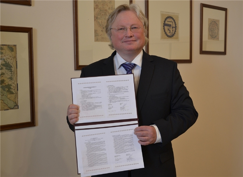 The Pro-Rector for Partnerships of Vilnius University holding the signed TRCCS Cooperation Agreement